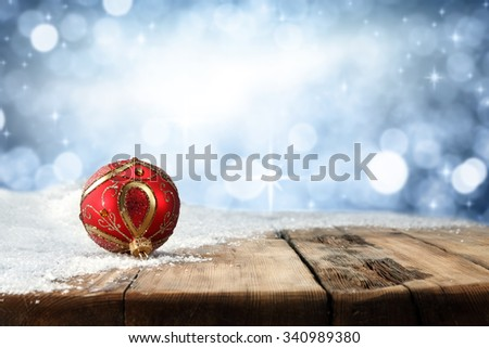 wooden table snow and red balls space  - stock photo