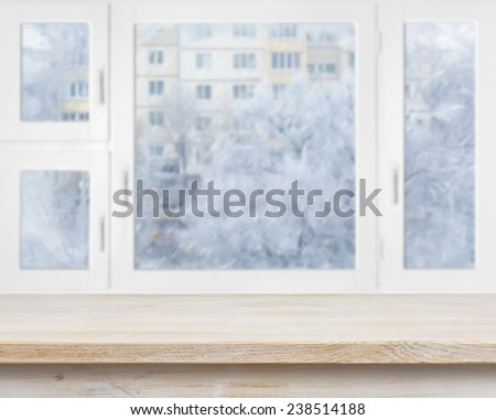 Wooden table surface over frosty window background - stock photo