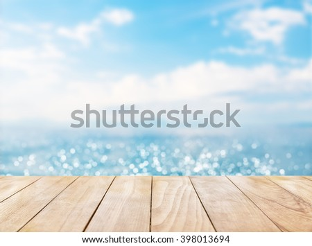 Wooden table top on blue sea and white sand beach background - stock photo