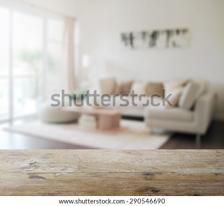 wooden table top with blur of modern living room interior as background - stock photo