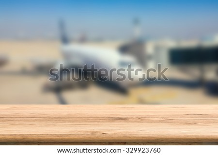 wooden table with airplane blurred background - stock photo