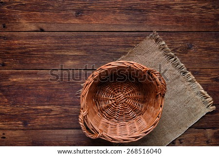 wooden table with basket on burlap texture background with copy space - stock photo