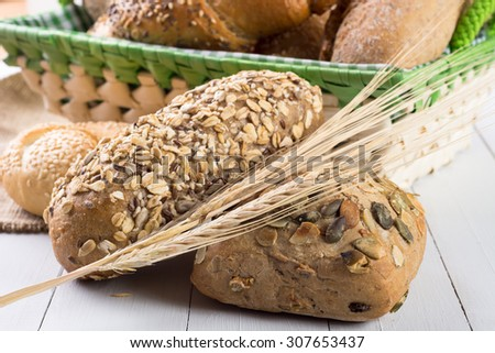 Wooden table with bread rolls in green basket