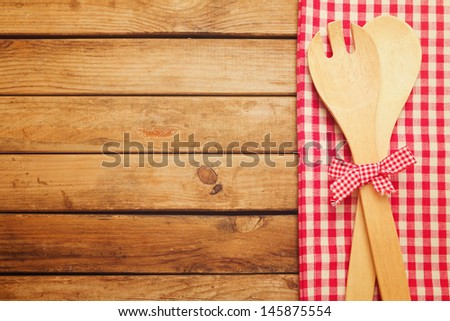 Wooden table with checked tablecloth and spoons - stock photo