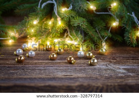 wooden table with defocused christmas  lights and glass decorations - stock photo