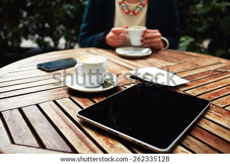 Wooden table with empty blank screen tablet, cup of cappuccino and bill check with money and cell phone on foreground, elegant well dressed woman drink coffee on background - stock photo