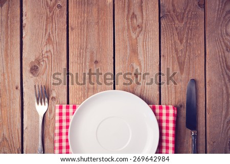 Wooden table with empty plate. View from above - stock photo