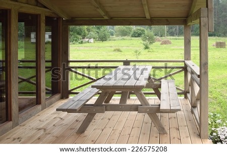 Wooden table with folding benches on a terrace - stock photo
