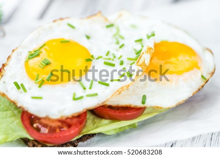 Wooden table with Fried Eggs (on a Sandwich) as detailed close-up shot