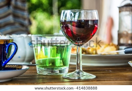 Wooden table with glass of red vine, water, coffee, sugar bowl and dessert, outdoor in summer day in garden