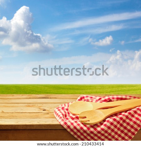 Wooden table with kitchen utensil over green meadow and blue sky - stock photo