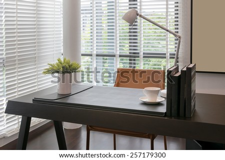 wooden table with lamp and books in modern working room interior - stock photo