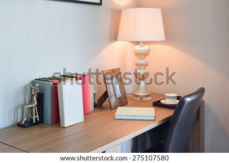 wooden table with reading lamp and books in modern working room interior - stock photo