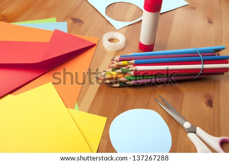 wooden table with scissors, pencils and drawing paper - stock photo