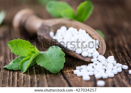 Wooden table with Stevia sweetener pills (selective focus; close-up shot)