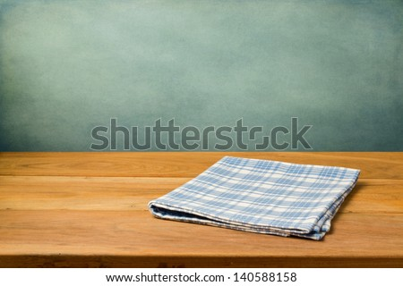 Wooden table with tablecloth over grunge blue wall - stock photo