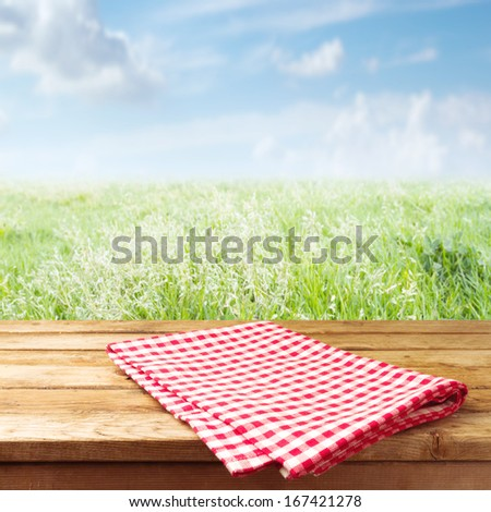 Wooden table with tablecloth over meadow - stock photo