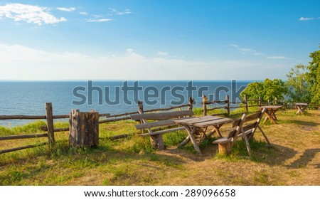 wooden tables and benches in the meadow on a steep bank of the Volga River - stock photo
