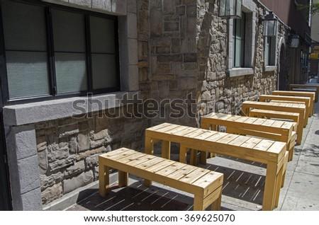 Wooden tables and benches standing in a row on a city street. New York, Manhattan. - stock photo
