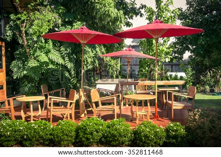Wooden tables and chairs under red umbrellas  in the garden - stock photo
