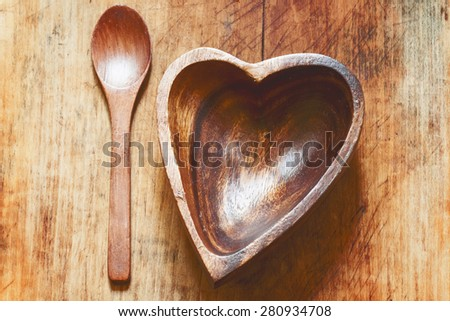 Wooden tableware: a heart-shaped bowl and spoon on the old board, selective focus - stock photo