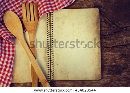 Wooden tableware and a notebook for recipes on the old board. Retro style.
