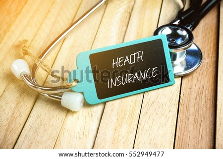 Wooden tag written with HEALTH INSURANCE and stethoscope on wooden background. Medical and Healthcare Concept.