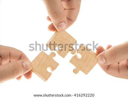 Wooden Teamwork - group of people holding wood puzzle pieces. three hands. Isolated on white background - stock photo