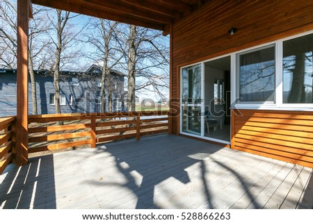wooden terrace of wooden cottage on sunny day in the forest