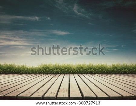 wooden terrace with fresh spring green grass and blue sky vintage style