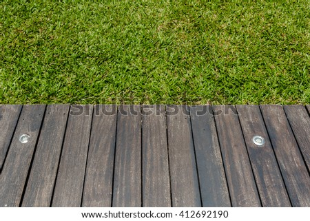 wooden terrace with groundlights lighting water proofed and green grass background