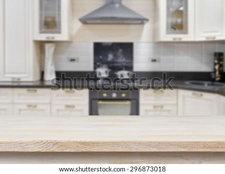 Wooden textured table over blurred kitchen vintage interior background - stock photo