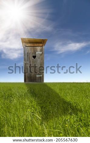 Wooden toilet, green field, blue sky - stock photo