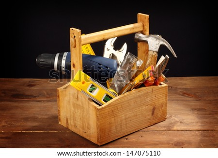 wooden tool box at work on a black background - stock photo