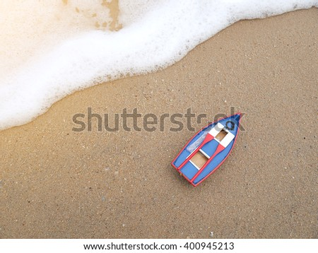 Wooden toy boat on the beach in summer season with bubble sea wave ...