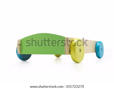 Wooden toy car against white background with colorful wheels. - stock photo