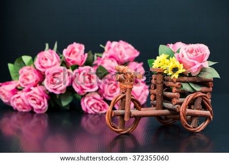 Wooden toy car with bouquet of pink roses on black background - stock photo