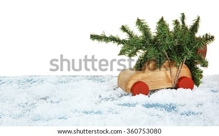 Wooden toy car with Christmas tree on a snowy table over white background - stock photo