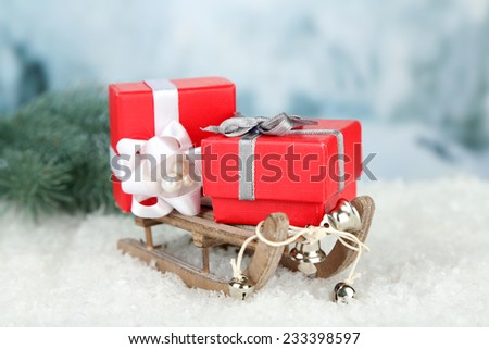 Wooden toy sledge with Christmas gifts  on nature background