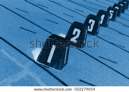 Wooden track number on plastic runway in a sports ground