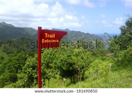 Wooden Trail Entrance Sign. Atlantic Ocean coastline, Dominica, Caribbean islands - stock photo