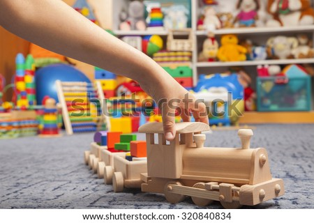 wooden train in the play room and many toys - stock photo