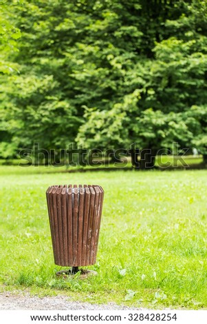 Wooden trash bin in the wood, against the forest - concept of clean nature and ecology - stock photo