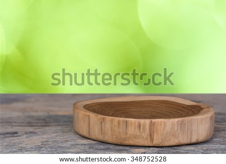 Wooden tray on old table with green blur background