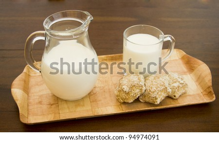 wooden tray with a cup and a jug of milk and gingerbread