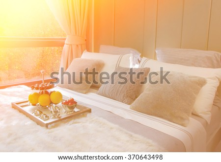 wooden tray with fresh fruits on cozy bed in hotel - stock photo