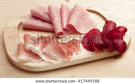 wooden tray with three types of cold cuts   - stock photo