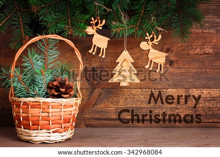 wooden tree decorations in the shape of a Christmas tree and reindeer weigh on fir branch near the basket with cone and fir branches on a brown wooden background with greetings for the merry christmas
