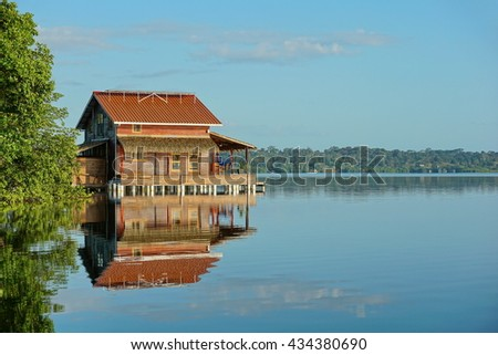 Wooden tropical home on stilts over calm water in a bay, Bocas del Toro archipelago, Caribbean sea, Panama, Central America - stock photo