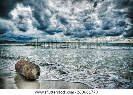 wooden trunk by the shore under a scenic sky - stock photo